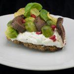 Hirschfilet, Zaziki, Rosenkohl, Kartoffelchip, Granatapfel und Basilikum auf Vollkornbrot